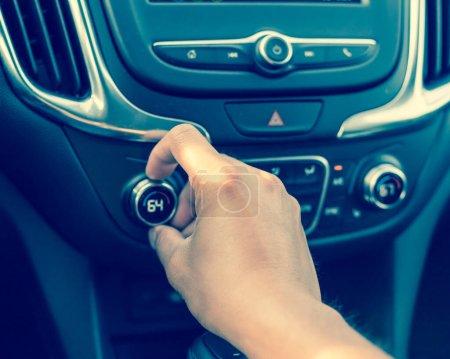 Photo pour Bouton de rotation de main gauche sur la température de refroidissement moderne de voiture ajustent au degré de 64 Fahrenheit F. Main mâle asiatique sur l'intérieur de voiture de climatiseur de tableau de bord - image libre de droit