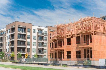 Photo pour Quartier de développement côté rue avec unités locatives en construction à North Dallas, Texas, États-Unis. Cadre en bois du complexe d'appartements de cinq étages avec grand patio près des bâtiments achevés - image libre de droit