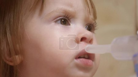 Photo for Child is sick and breathes through an inhaler. close-up. little girl treated with an inhalation mask on her face in hospital. Toddler treats flu by inhaling inhalation vapor. - Royalty Free Image