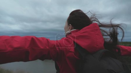 Photo for Free happy girl traveler goes to edge of mountain with outstretched arms, wind is waving her hair. young woman travels with backpack, looks from top of mountain, enjoying beautiful landscape and river - Royalty Free Image