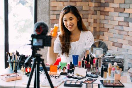 Photo pour Charmante asiat enregistrement vlog. Blogueur de beauté présentant des cosmétiques maquillage devant la caméra - image libre de droit