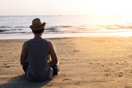 Photo pour Jeune mâle de voyage de Routard pratiquant la méditation Zen sur la plage de mer tropicale extérieure sur la silhouette pendant le coucher du soleil-concept de pose de yoga calme et sérénité. - image libre de droit