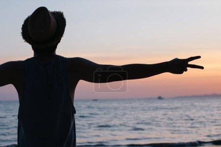 Photo pour Silhouette dos de jeune mâle voyage Routard faire la paix v signe doigt contre le coucher du soleil et tropical d'été océan plage fond. - image libre de droit