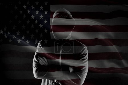 Photo for Double exposure of concept of criminal in USA with silhouette of male with crossed hands in hood and flag - Royalty Free Image