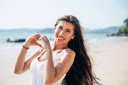 Photo for Young woman making heart shape gesture. Reflection of love.,Young woman making heart shape gesture. Reflection of love. - Royalty Free Image