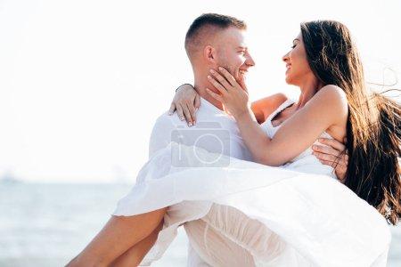 Photo pour Couples dans l'amour regardant l'un l'autre comme homme lève la femme, couple dans l'amour regardant les uns les autres comme homme lève la femme - image libre de droit