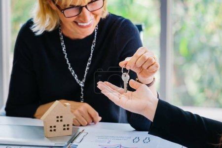 Foto de Mujer de negocios adulta sonriendo y dando la llave a la mano de la cosecha mientras está sentado en el escritorio con el modelo de casa en la oficina de la agencia inmobiliaria - Imagen libre de derechos