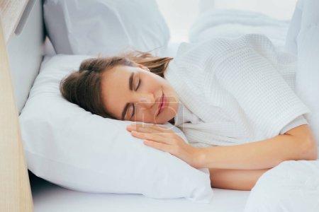 Photo pour Jeune femme heureuse avec les yeux fermés dormant sur le bâti avec le visage calme et paisible - image libre de droit