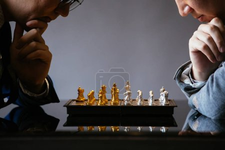 Photo for Two unrecogniazble businessmen thinking over moves while playing chess against gray background - Royalty Free Image