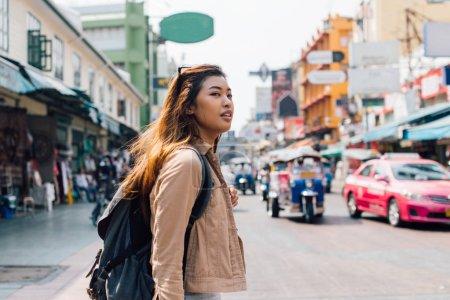 Photo pour Jeune femme asiatique heureuse de touriste marchant et regardant loin sur la route de Khao San en été pendant le voyage à Bangkok, Thaïlande - image libre de droit