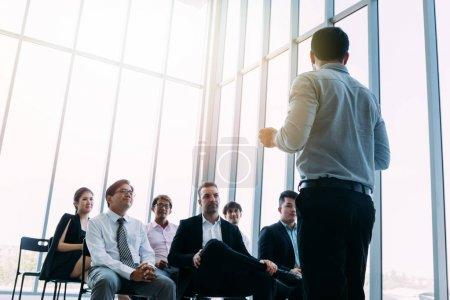 Photo pour D'en bas de l'homme d'affaires restant devant des collègues dans la salle ensoleillée légère et faisant la présentation - image libre de droit
