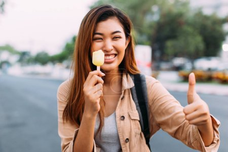 Photo pour Young Asian woman showing thumbs up with popsicle ice cream in outdoor scene. Female with good teeth health - image libre de droit
