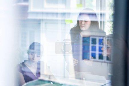 Foto de Grupo de mujeres de negocios asiáticas y caucásicas que sostienen documentos con reflejo de vidrio de la construcción de oficinas - Imagen libre de derechos