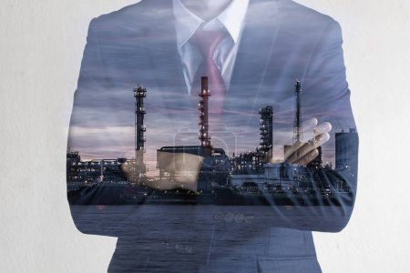 Double exposure image of Business man with petroleum oil refinery plant beside river
