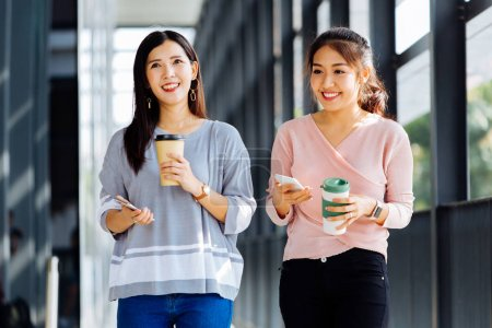 Photo for Young Asian business women talking while walking in office building in casual wear. Two girls strolling and discussing outdoors - Royalty Free Image