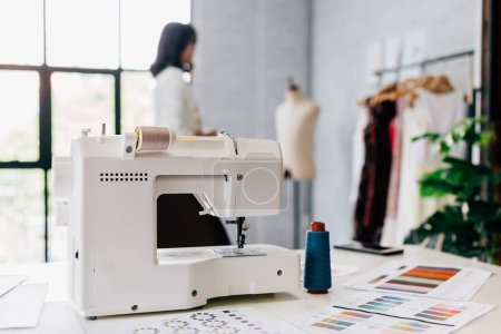 Photo pour Machine à coudre automatique blanche et motifs sur table en atelier avec styliste féminine floue sur fond - image libre de droit
