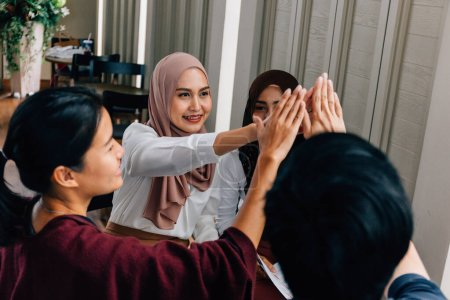 Photo for Group of multicultural Asian ladies smiling and doing high five after finishing project during work in elegant cafe - Royalty Free Image