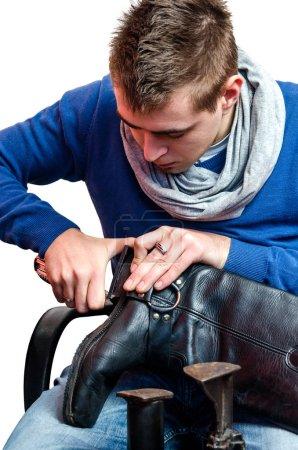 Shoemaker repairing a heel on white background