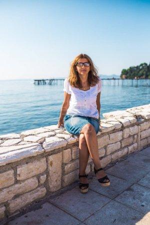 Photo pour Femme détendant sur la jetée, Grèce - image libre de droit