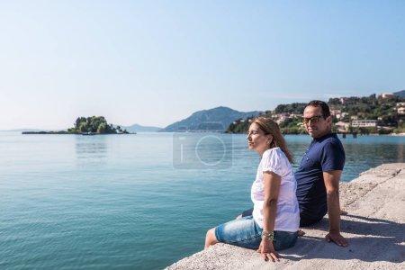Photo pour Touristes de femme et d'homme détendant sur la jetée, Grèce - image libre de droit