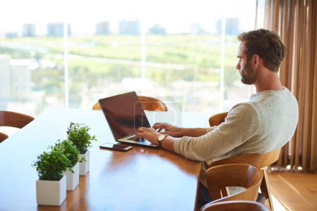 Modern man sitting at dining table with his laptop working