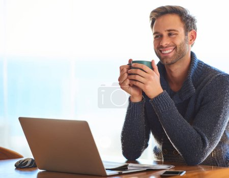 Photo for Handsome young caucasian man, happily smiling while holding his coffee mug for warmth in the morning, as he prepares for work with a positive attitude. - Royalty Free Image