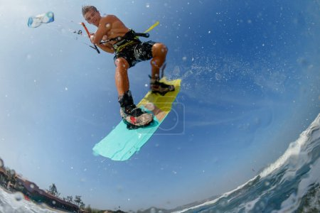 Photo for Professional kite surfer performing acrobatic trick while rides waves - Royalty Free Image