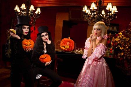 Halloween concept: sexy ladies vampire with halloween pumpkins assailing blond girl