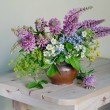 Still life with a bouquet of wild flowers in a cla...