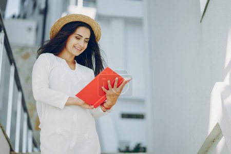 Photo for Young and pretty girl in a summer city standing near stairs with red book - Royalty Free Image