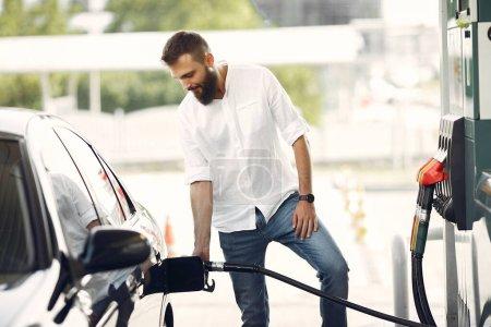 Przystojniak wlewa benzynę do cysterny.