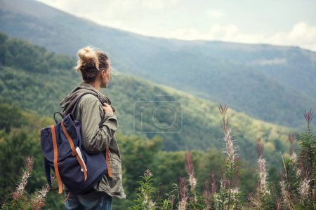 Photo for Young woman traveler  with backpack hiking in the mountains, relaxing and enjoying a beautiful nature during vacation . - Royalty Free Image