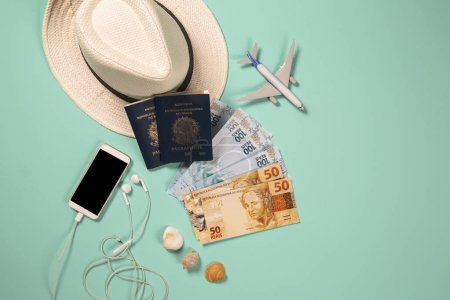 Photo for Items for summer vacation: telephone, passport, money and airplane. Blue background, top view. - Royalty Free Image