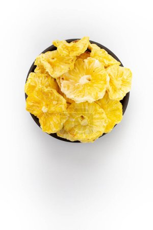 Photo for Dried Pineapples in round bowl on white background, top view - Royalty Free Image