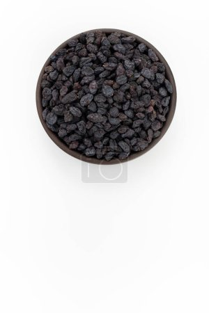 Photo for Black raisins in round bowl on white background, top view - Royalty Free Image