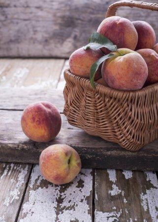 Photo pour Gros backet avec fruits naturels mûrs frais pêches sur une vieille table en bois, placer sous le texte. - image libre de droit