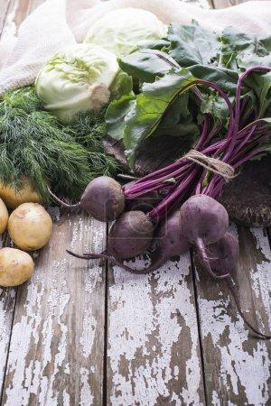 Photo pour Ingrédients naturels fraîchement cueillis pour la cuisson du plat végétalien - betterave, pomme de terre, chou sur fond en bois, place pour le texte. - image libre de droit