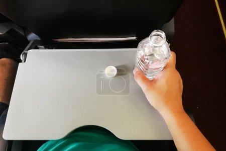 Passenger holding mineral water bottle in aeroplane cabin.  Advice to drink lots of water to keep  oneself hydrated on long haul flight.