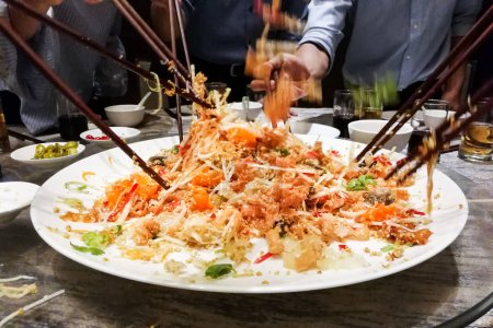 Photo for People tossing yee sang or yusheng during Chinese New Year , traditional practice in Malaysia and Singapore for luck and prosperity - Royalty Free Image