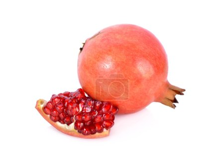 whole and cut fresh pomegranate fruit on white background