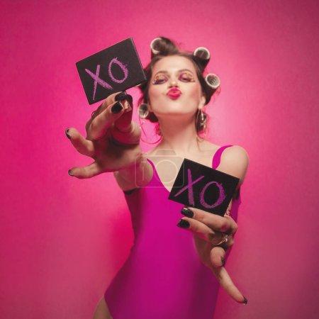 glückliches Mädchen mit kleinen Tafeln und Text Xo darauf in den Händen posiert