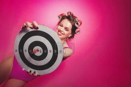 freche Mädchen mit Darts posiert auf rosa Hintergrund im Körper, mit c