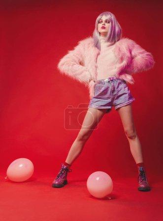 freche Mädchen auf rosa Hintergrund in Körper, Pelzmantel, Stiefel. schön
