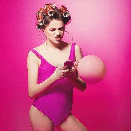 Freches Mädchen mit rosa Luftballon tippt wütende Nachricht auf Smartphone