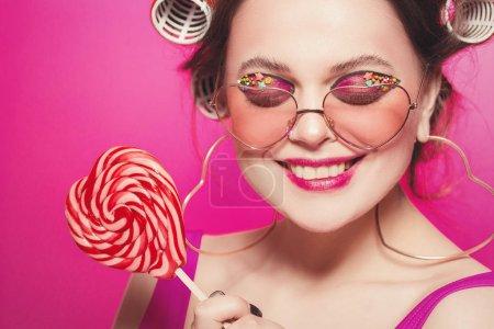 glückliches Mädchen mit Bonbonherz posiert auf rosa Hintergrund im Körper, w