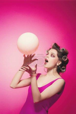 freche Mädchen mit rosa Ballon auf rosa Hintergrund im Körper, mit Lockenwickler auf dem Kopf. hübsche sexy Frau mit süßem Make-up posiert attraktiv im Studio