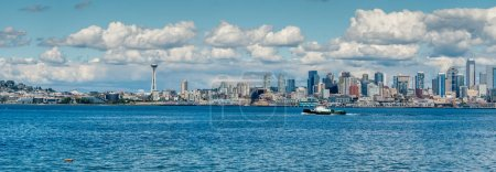 A panorama view of the Seattle skyline with puffy clouds above.