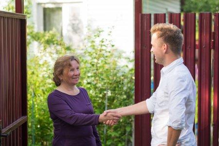 Les voisins discutent des nouvelles, debout à la clôture. Une femme âgée qui parle avec un jeune homme. Ils sont satisfaits de cette rencontre