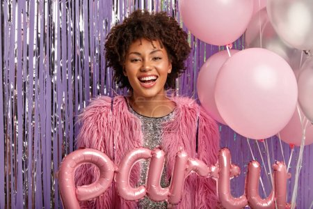 Photo pour Indoor shot of happy dark skinned Afro woman comes on corporate party, has fun in good company, wears rosy fur coat, holds balloons, has broad smile, minimal makeup. - image libre de droit