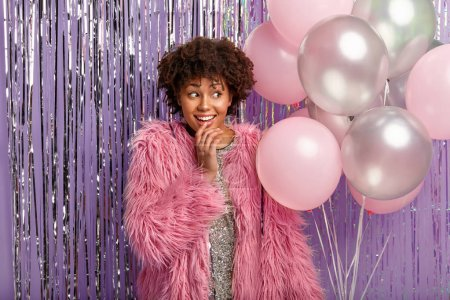 Photo pour Glad dark skinned female in sparkling dress and pink coat, holds balloons, focused aside with cheerful expression, gathers with friends on special occasion - image libre de droit
